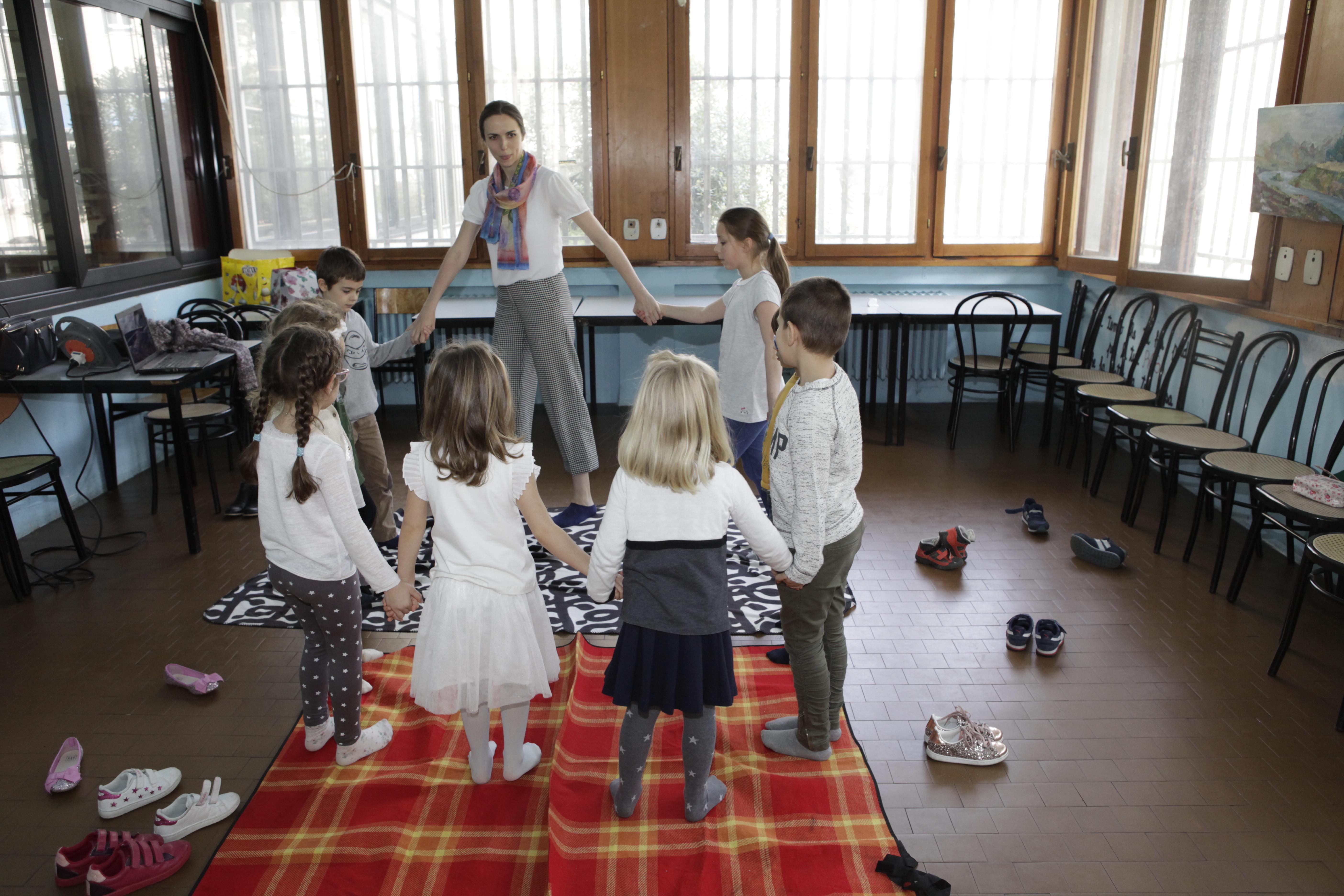 """Milano lituanistinės mokyklėlės """"Aitvaras"""" vaikai su akordeoniste Aurelija Matulevičiūte. Organizatorių nuotr."""